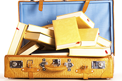 a travel suitcase full of books on a white background