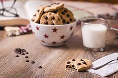 Closeup of chocolate chip cookies on stars bowl and milk glass over a wooden background. Image focused in cookie bite