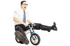 Nerdy young male with tie riding a small bicycle isolated on white background