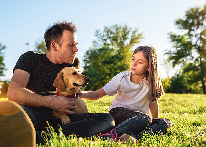 father and daughter talking, with dog in park